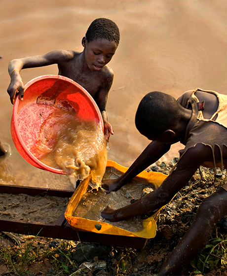 Boys pan for gold on a riverside in eastern Congo, where bitter ethnic conflict has left tens of thousands dead.